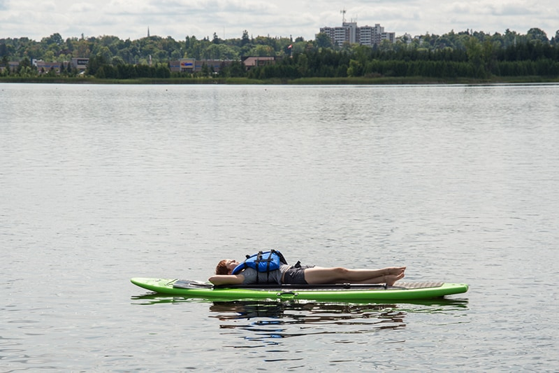 A person laying down on a paddleboard as it floats on Island Lake, with a view of the town of Orangeville on the far side of the lake.