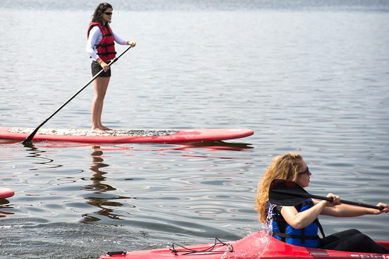 A person kayaking past a paddleboarder at Island Lake Conservation Area.
