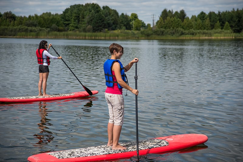 Park visitors stand-up paddleboarding on Island Lake.