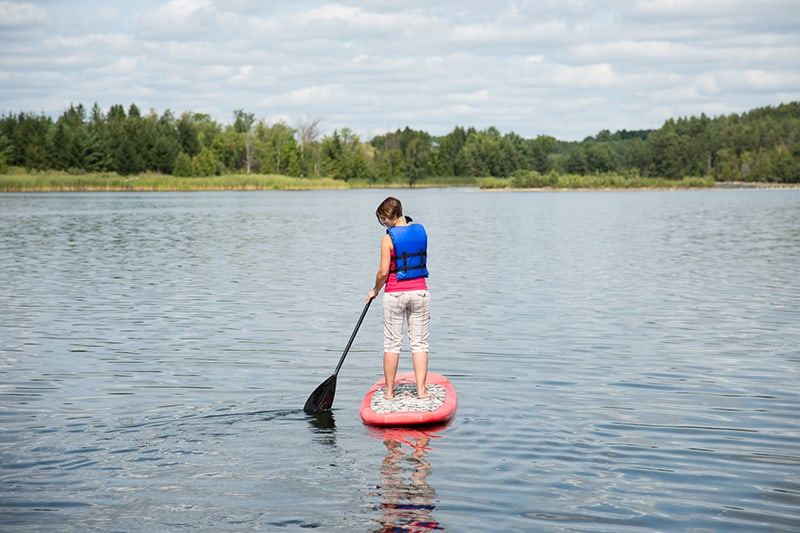 A person paddleboarding across the lake in the summer.