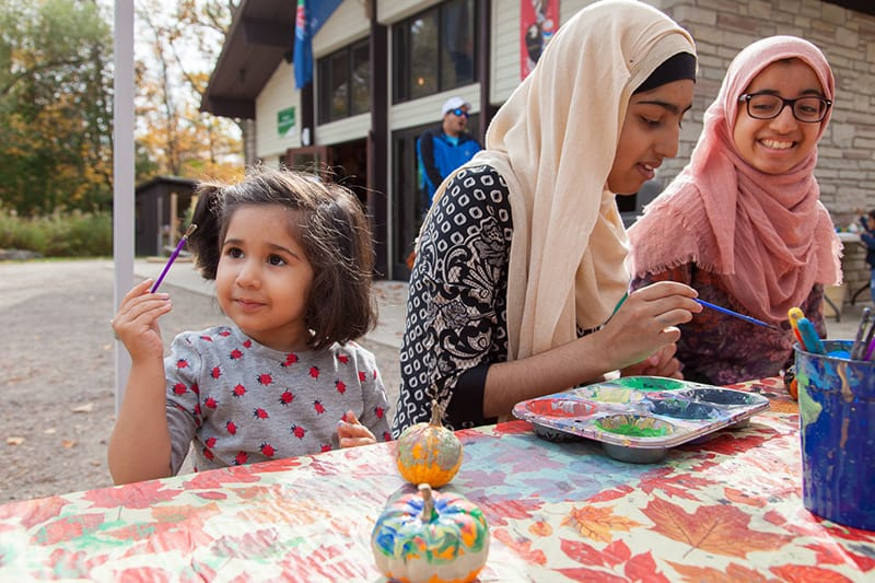 A child and two adults paint mini pumpkin gourds at the fall festival at Terra Cotta outside the Welcome Centre.