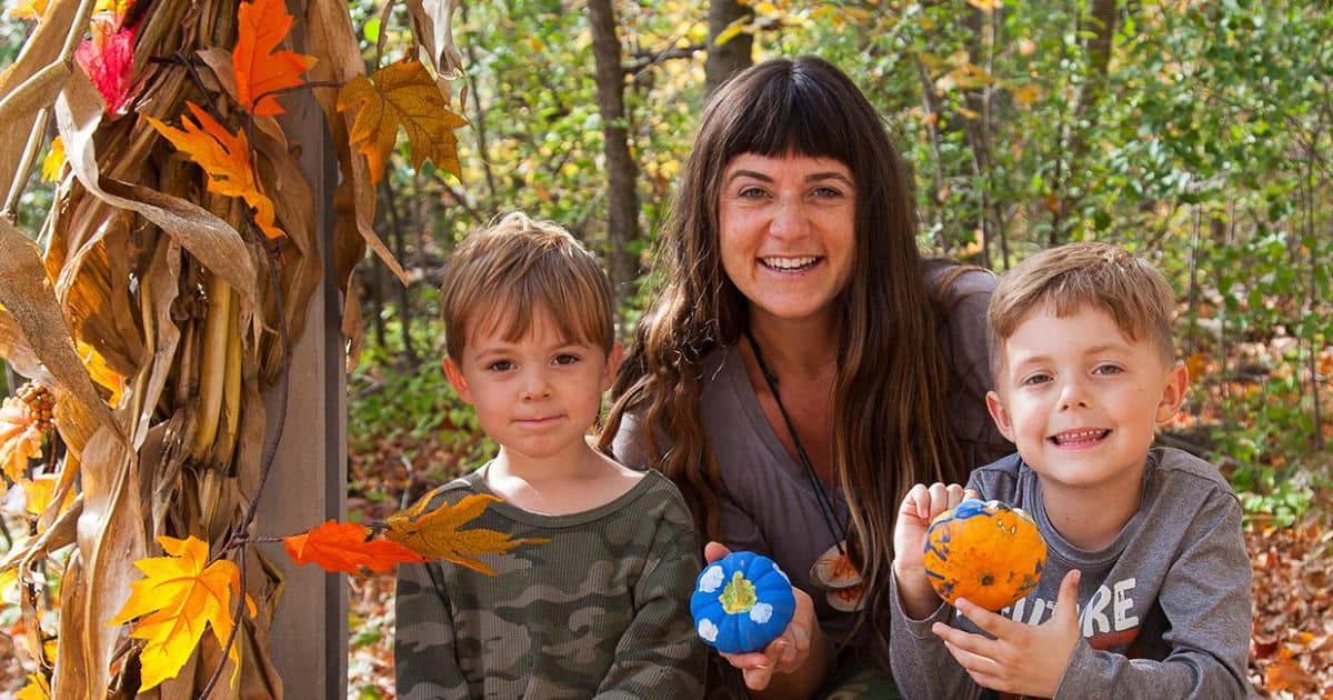 A family poses together at the fall festival at Terra Cotta on hay bales surrounded by pumpkins.