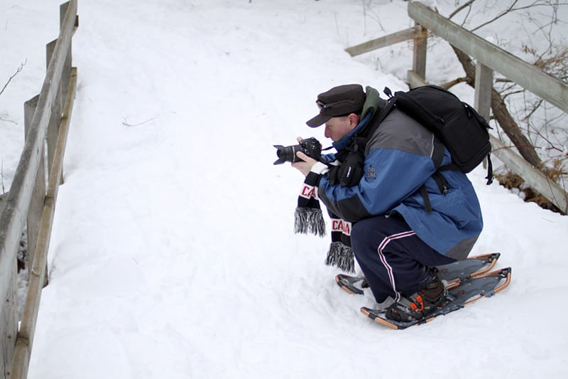 A photographer on snowshoes crouches down to take a photo in the snow.