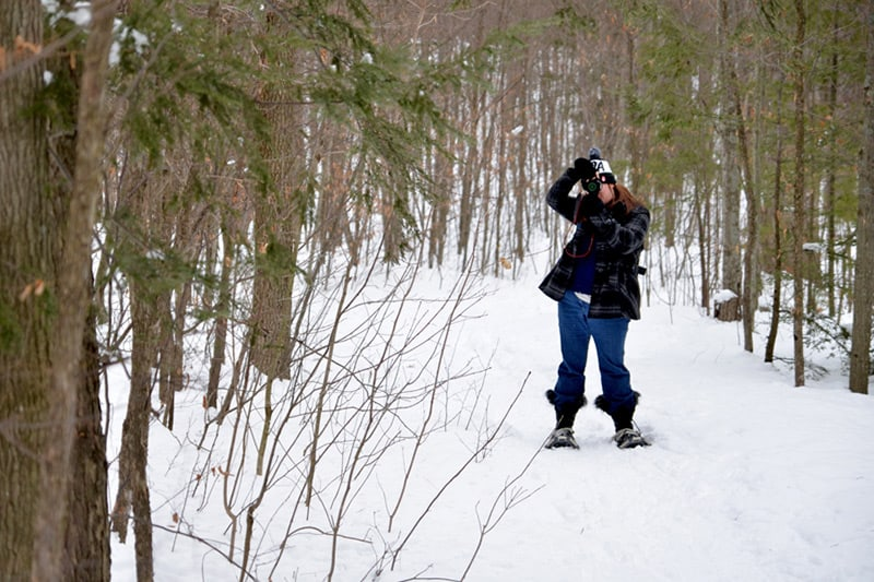 A park visitor on snowshoes stops on a snowy trail to take photos.