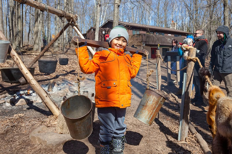 A child holding buckets of sap on their shoulders using a traditional yoke, at the annual maple syrup festival.