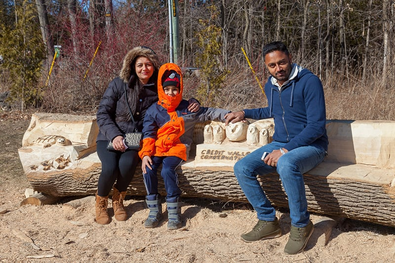 A family sits on a bench carved out of a log at Terra Cotta.