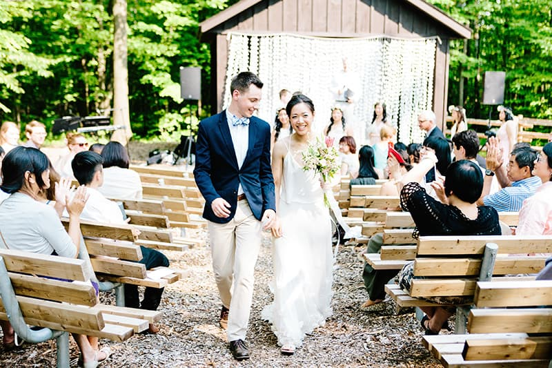 a couple walking down the aisle after getting married at an outdoor pavilion with wedding guests in the background