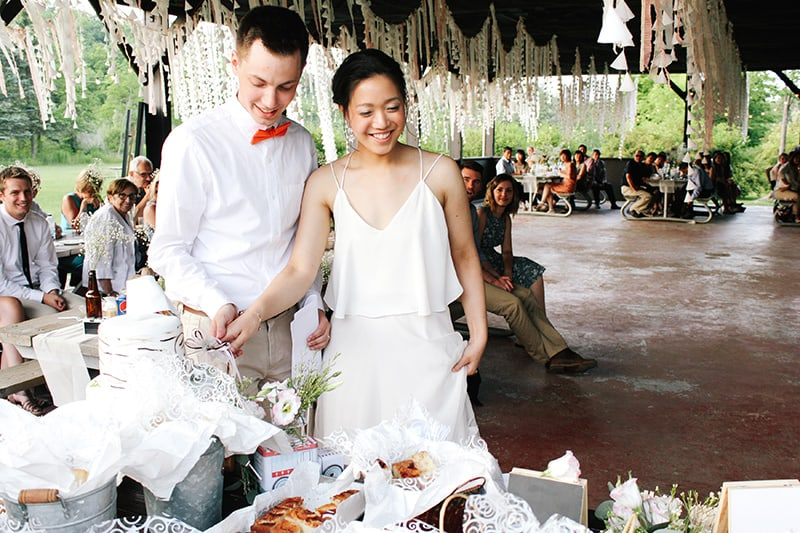 a bride and groom cutting their cake under an outdoor pavilion with guests and decorations in the background