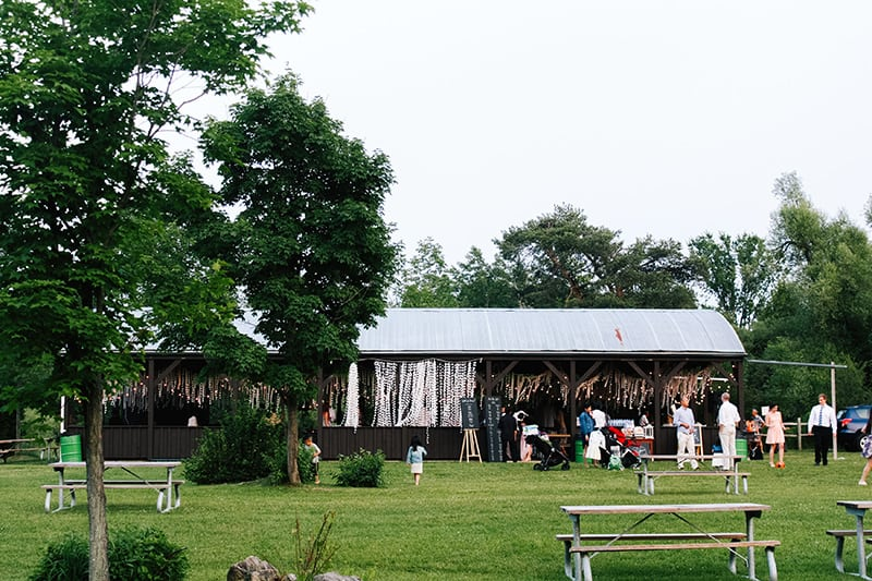 people standing at an outdoor pavilion that's decorated for a wedding reception