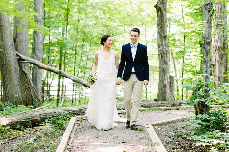 bride and groom walk down a gravel path holding hands surrounded by trees