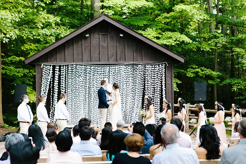 a couple standing on an outdoor stage getting married with guests sitting on benches