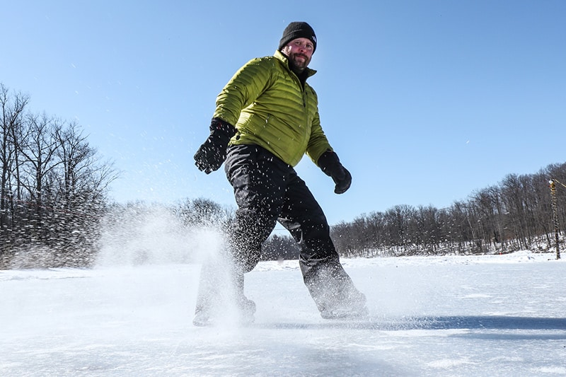 A skater coming to a stop on the ice with trees in the background