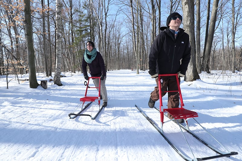A man and a woman kicksledding along Terra Cotta Lane with trees in the background