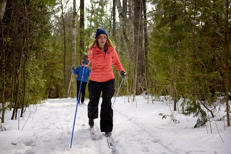 Two people cross-country skiing through a wooded section of trail.