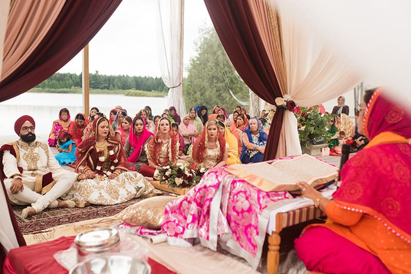 A group of people dressed in colourful attire for a wedding on a water amphitheatre with a lake and trees in the background