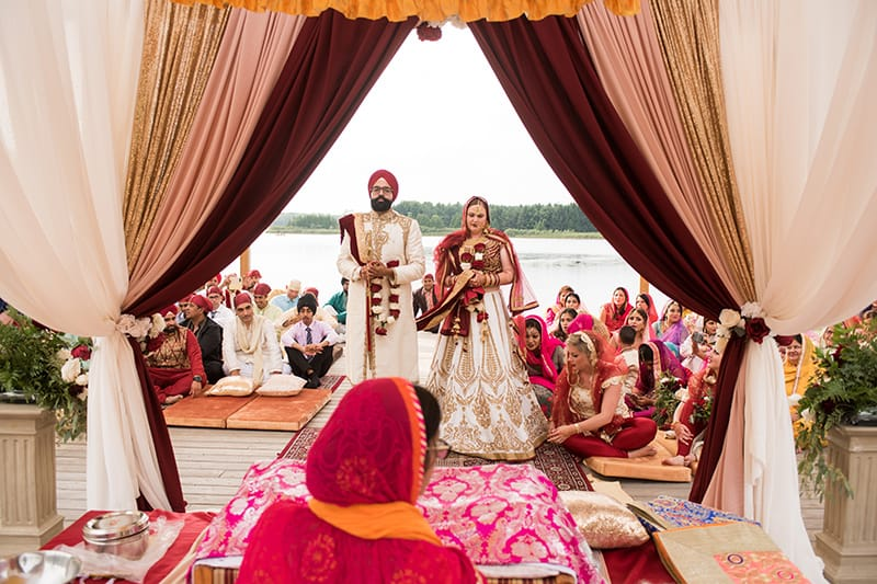 a couple standing at the alter getting married on a water amphitheatre with guest behind them in colour attire. A lake and trees are in the background