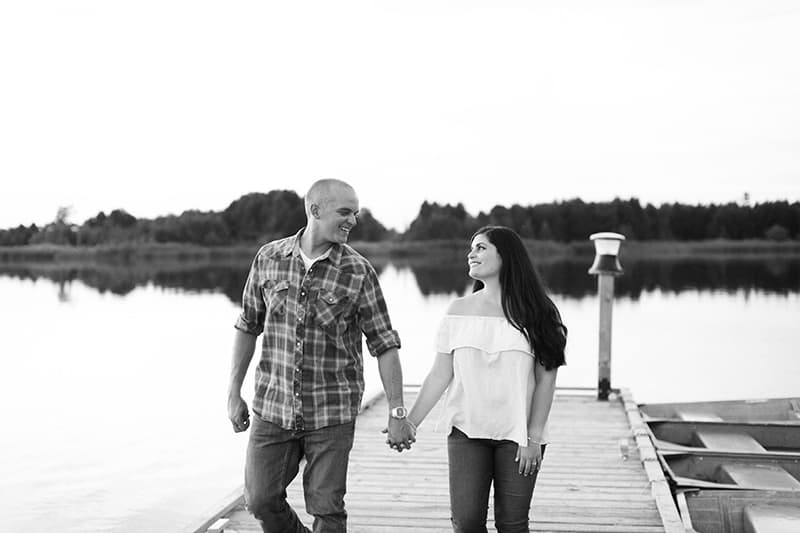a couple holding hands smiling at each other while walking on a dock at a lake