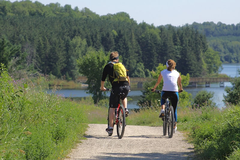 Two cyclists ride their bikes along the trail at Island Lake Conservation Area.