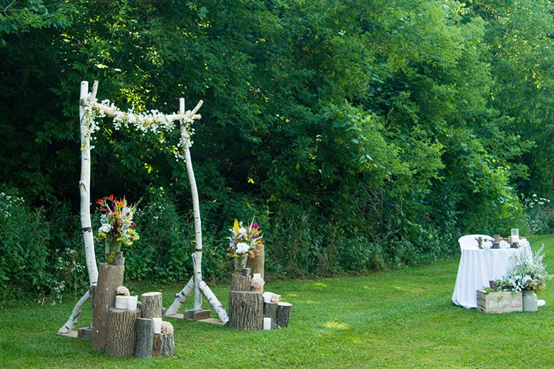 a wood archway set up with flowers for a wedding with trees in the background