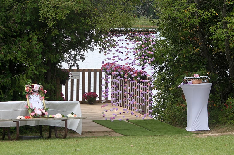a pier surrounded by trees and overlooking a lake is decorated for a wedding