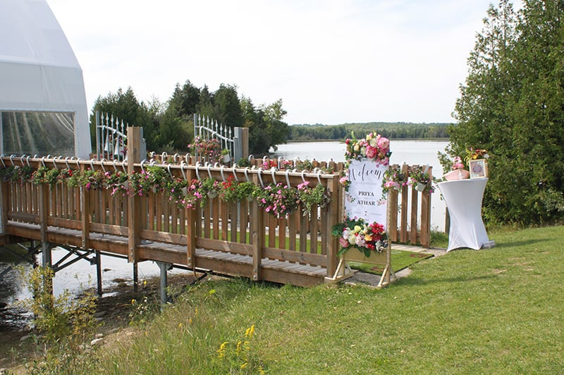 A walkway leading to a water ampthitheatre decorated for a wedding with a lake and trees in the background