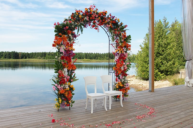 A decorated wedding archway on a stage with a lake and trees in the background