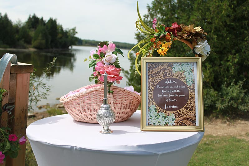 A table with flowers and a framed message to wedding guests with a lake and trees in the background