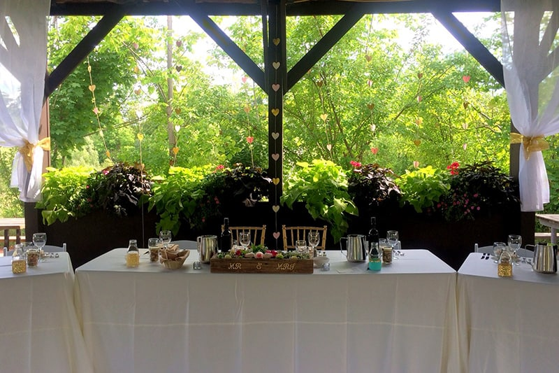 a table decorated for the bride and groom at an outdoor pavilion with trees in the background