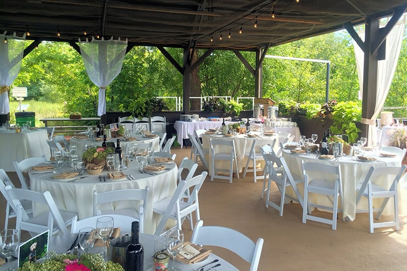 decorated tables set up for a wedding under an outdoor pavilion with trees in the background
