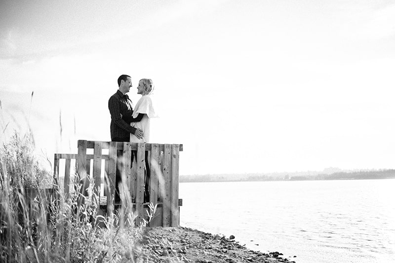 A couple standing on a wood pier looking into each others eye with a lake in the backgrouned