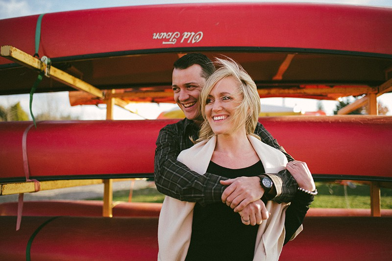 a couple hugging and smiling with a rack holding canoes in the background