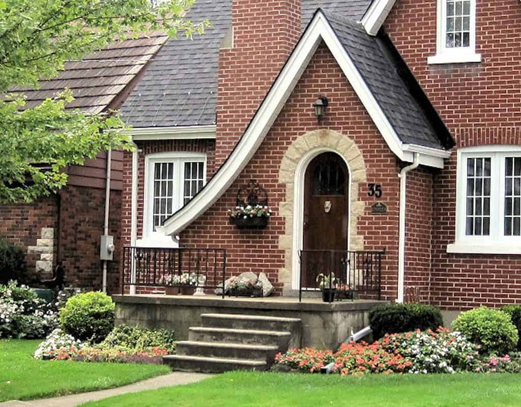 A residential, red-brick home with a stone front porch and separate building beside it.