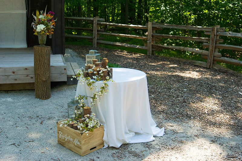 a table set up with some flowers beside an outdoor stage with trees in the background
