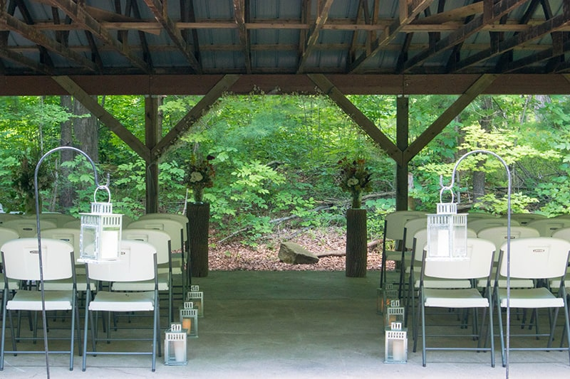 chairs set up in an outdoor pavilion with a centre aisle and flowers and trees in the background