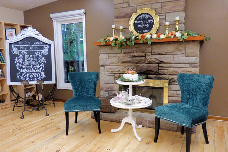 two chairs set up in front of a fireplace with signs and wedding decor