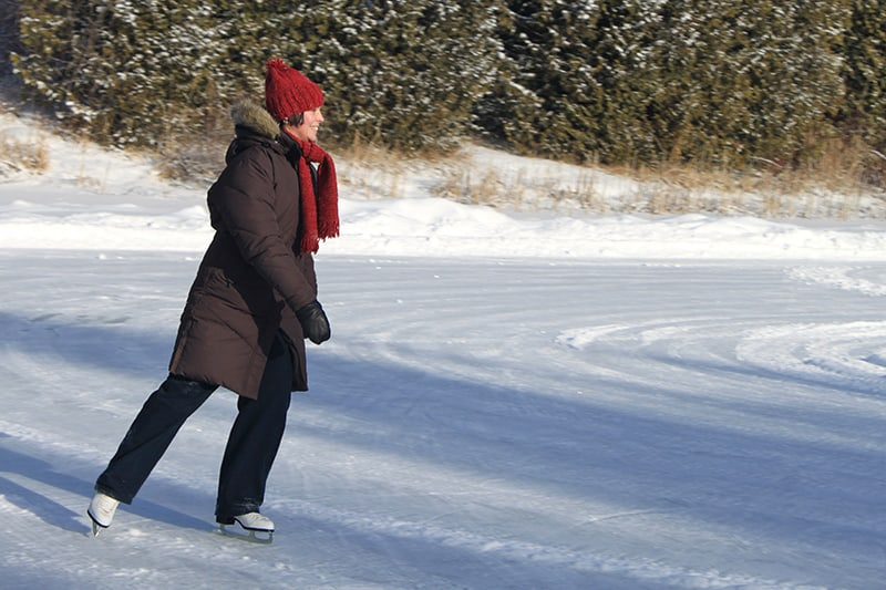 A woman skating on a frozen pond at Island Lake Conservation Area with trees in the background