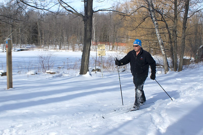 A man cross-country skis past the frozen lake at Terra Cotta Conservation Area.