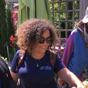 A CVC staff member standing with two adult program attendees looking at a raised garden.