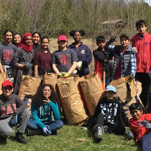 A large group of students posing together with yard bags full of pulled invasives.