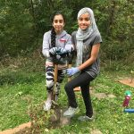 Two students pose with a shovel in the ground behind a sapling they just planted.