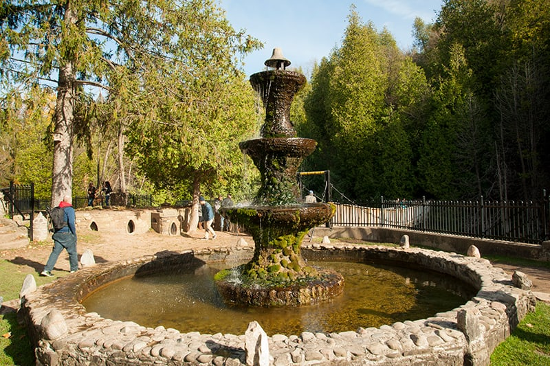 The tall stone Belfountain fountain with mosses growing over it.