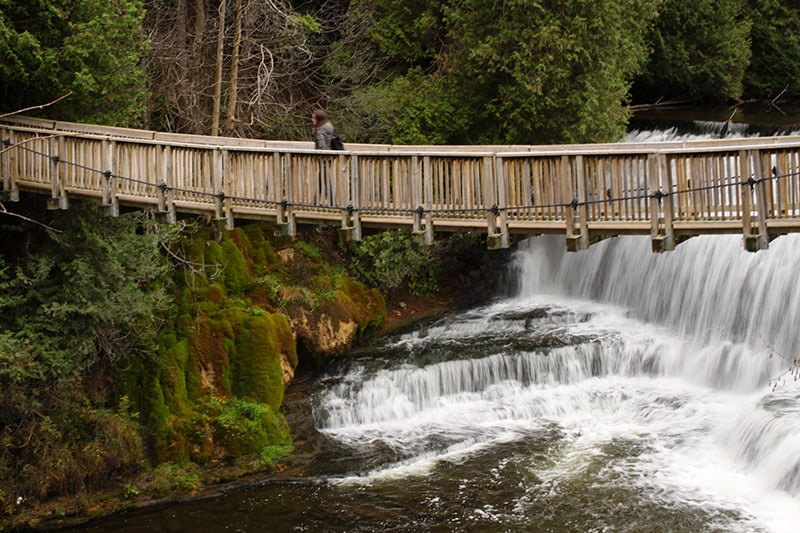 A park visitor with a backpack walks across the suspension bridge. Beyond the bridge is the dam and water falling onto rocks below.