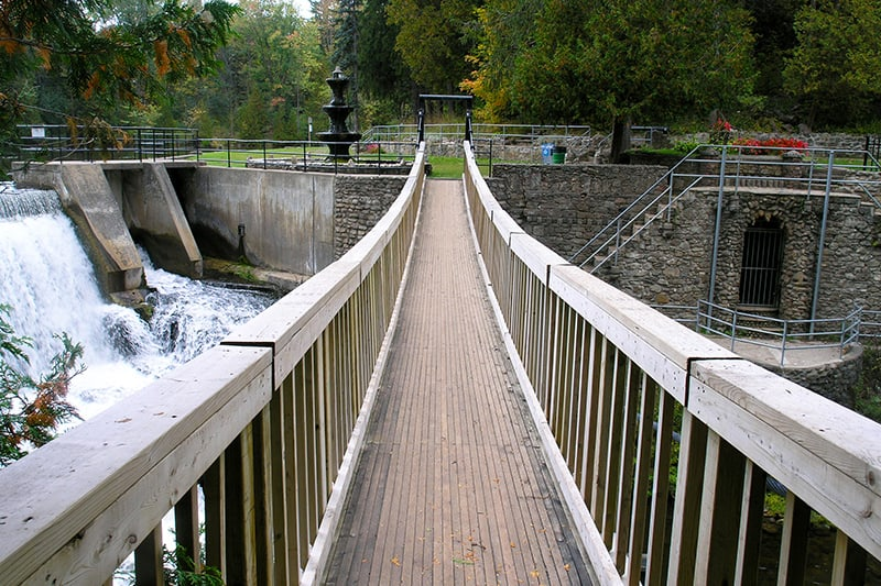 A long suspension bridge stretches over the river, downstream from the dam and falls, The Belfountain fountain can be seen on the other side as well as an opening in the side of the stone wall below the bridge.