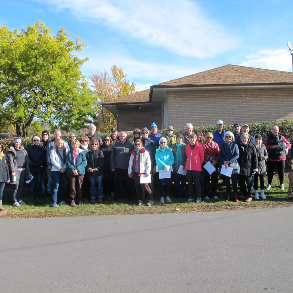 Group of staff, adults and children posing together outdoors at a Hungry Hollow SNAP event.