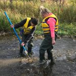 Two teens in a creek, wearing waders and safety vests, using nets.