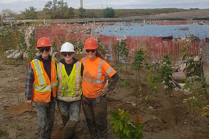 Three employees pose before a property with a pond wearing hardhats and safety vests.