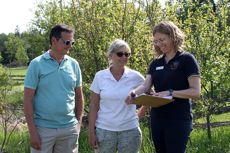 A CVC employee stands outside with two rural landowners, reviewing information on a clipboard.