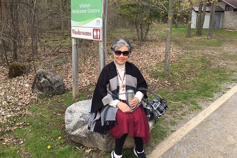 A park visitor sitting on a rock outside the Welcome Centre at Terra Cotta Conservation Area.