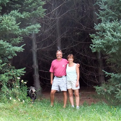 Two landowners stand in front of a forest on their property