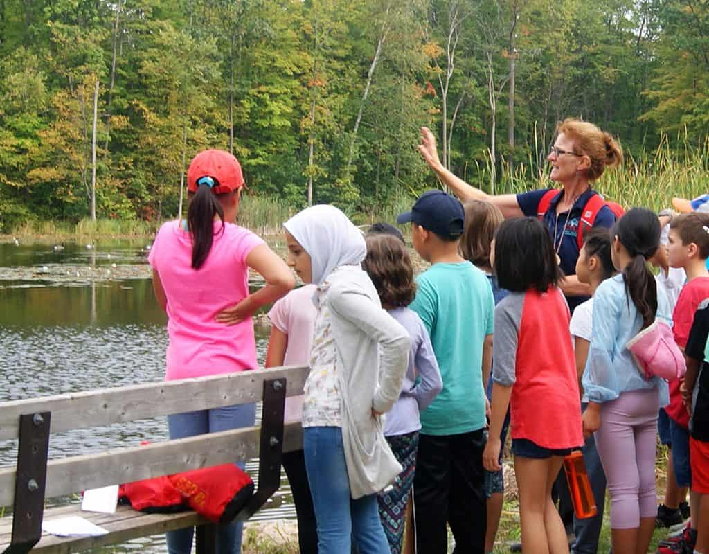 A teacher engages with a group of young students standing beside Wolf Lake at Terra Cotta.